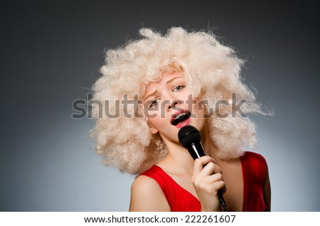 Young woman with mic in music concept - stock photo