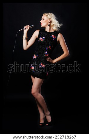 Young woman  with microphone singing in karaoke - stock photo
