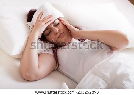 Young woman with migraine lying in bed and doing wraps  - stock photo
