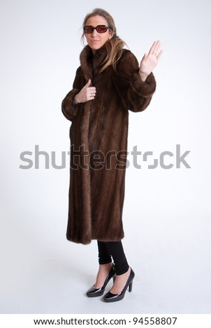 Young woman with mink coat and sunglasses - stock photo