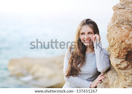 young woman with mobile phone on a beach - stock photo