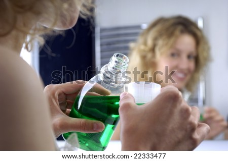 Young woman with mouthwash - stock photo