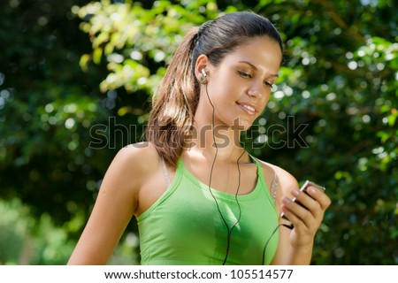 Young woman with mp3 player doing fitness in city park - stock photo