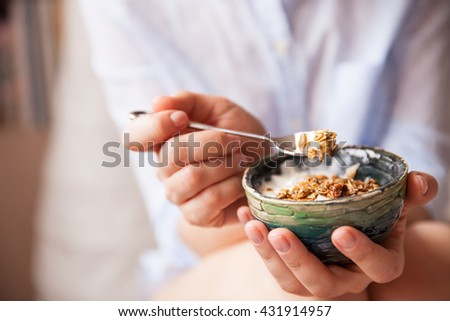Young woman with muesli bowl. Girl eating breakfast cereals with nuts, pumpkin seeds, oats and yogurt in bowl. Girl holding homemade granola. Healthy snack or breakfast in the morning.. - stock photo