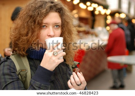 young woman with mulled wine and chestnut at christmass fair - stock photo