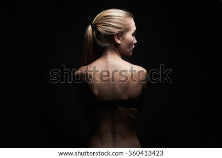 young woman with naked back over black background.sport body girl - stock photo