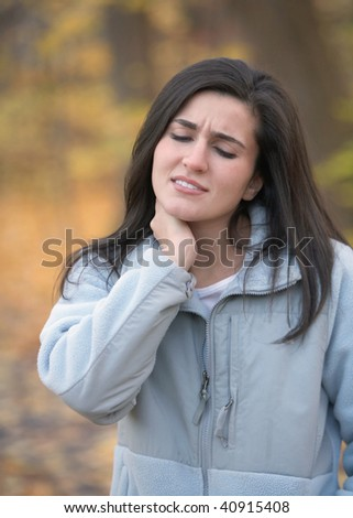 Young woman with neck pain outdoors in autumn - stock photo
