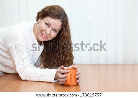 Young woman with orange mug in hands looking at camera on the table in office, copyspace - stock photo