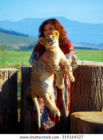 young woman with ornamental dress l playing with lion cub in nature. woman holding lion cub - stock photo