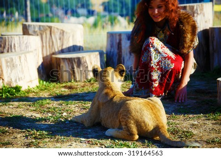 young woman with ornamental dress playing with lion cub in nature, with wolf fur - stock photo