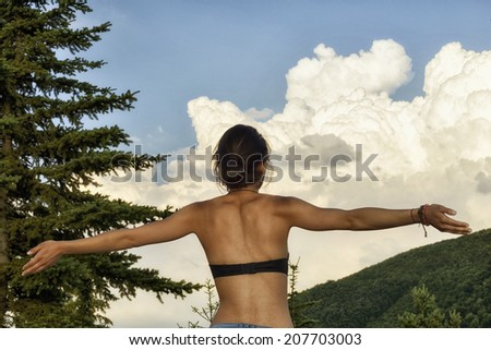 Young woman with outstretched arms is enjoys summer day in the mountains - stock photo
