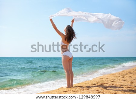 Young woman with pareo on the beach - stock photo