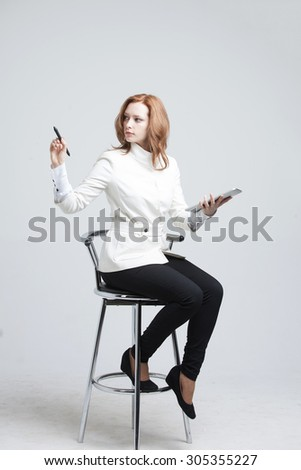 young woman with pen and tablet writes or shows on grey background - stock photo