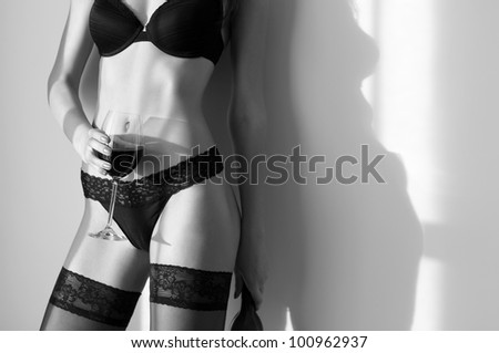 Young woman with perfect body with glass of wine - stock photo