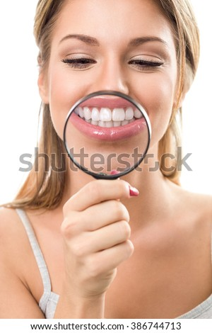 young woman  with perfect smile and healthy  teeth behind magnifying glass - stock photo