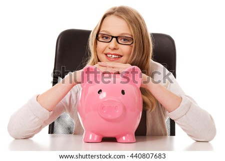Young woman with piggybank on the desk - stock photo