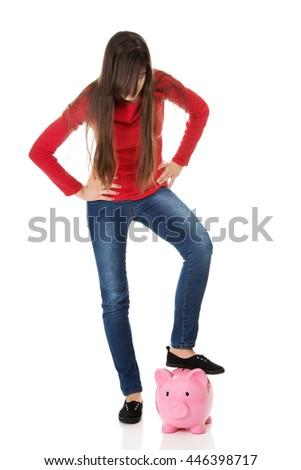 Young woman with piggybank under leg. - stock photo