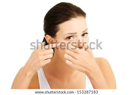Young woman with pimple on her face. Trying to squeeze it. Isolated on white background.  - stock photo