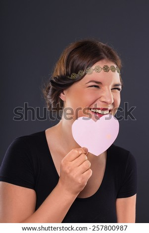 Young woman with pink heart on black background. studio  - stock photo