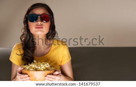 Young woman with popcorn and 3d glasses watching movie at home - stock photo
