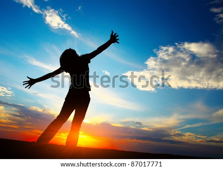 Young woman with raised hands on sunset sky background - stock photo