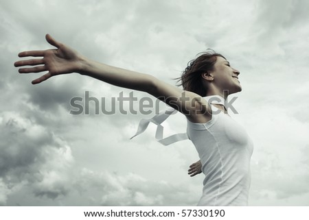 Young woman with raised hands over clouds background - stock photo