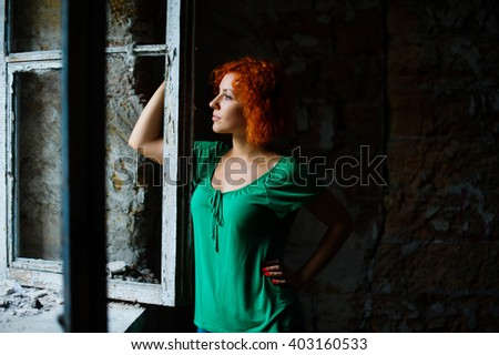 Young woman with red curly hair in green clothes standing near the big vintage wooden window. Beautiful girl in the old, retro grunge abandoned derelict house building.  - stock photo