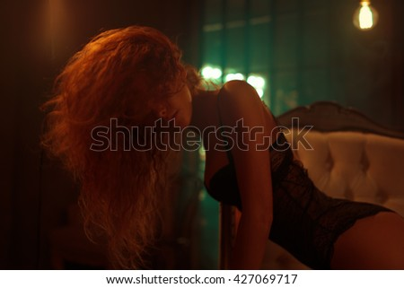 Young woman with red hair indoors sexy portrait. Vintage film style colors and out of focus effects. - stock photo