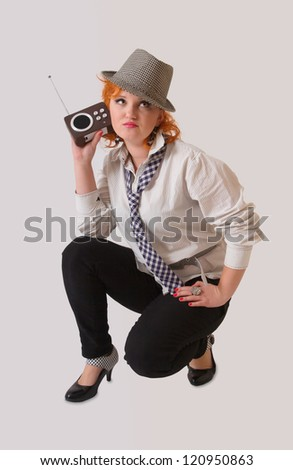 Young woman with red hair listening old radio - stock photo
