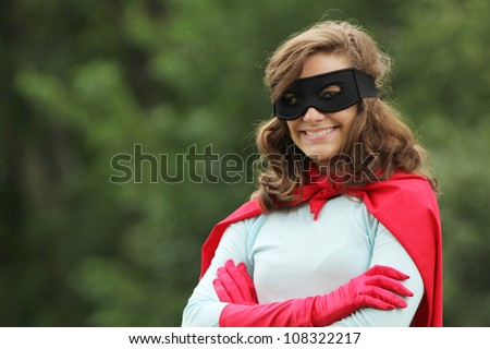 Young woman with red super hero kit smiling - stock photo
