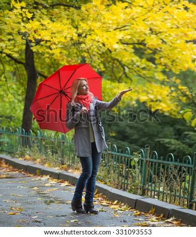 Young woman with red umbrella in beautiful autumn park - stock photo