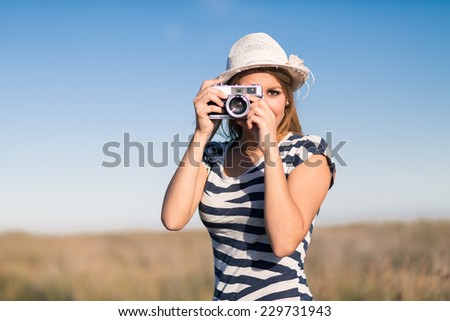 Young woman with retro photo camera outdoor - stock photo