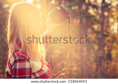 Young Woman with retro photo camera taking selfie shot outdoor hipster Lifestyle forest nature on background - stock photo