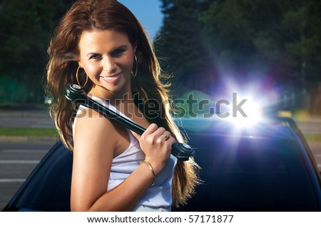 Young woman with screw key on car background. Bright flash effect. - stock photo