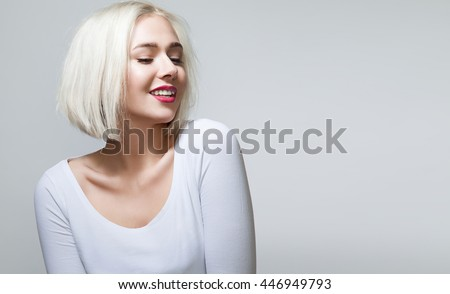 Young woman with shiny blond hair, red lips and pretty smile in white shirt - stock photo