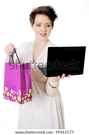 Young woman with shopping bag and laptop symbol of an internet shopping - stock photo