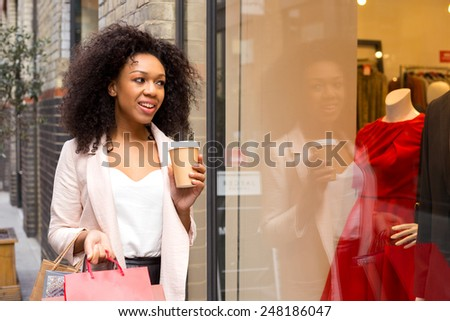 young woman with shopping bags and a coffee - stock photo