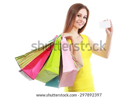 Young woman with shopping bags and credit card on a white background - stock photo