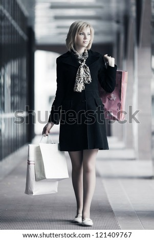 Young woman with shopping bags in a mall gallery - stock photo