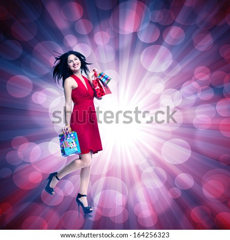 Young woman with shopping bags over glowing background. - stock photo
