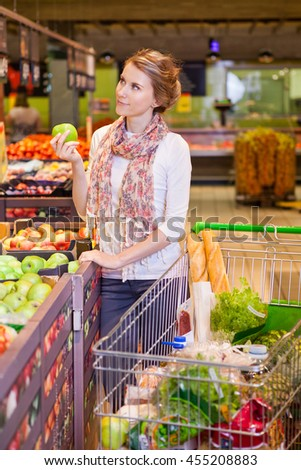 Young woman with shopping basket choosing apples in grocery store - stock photo