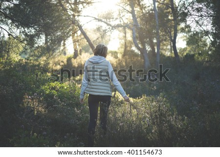 Young woman with short hair wearing a waistcoat in the middle of the forest at sunset surrounded by rosemary flowers enjoying the calm and the fragrance - stock photo