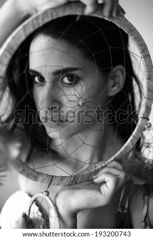 young woman with shy look through dream catcher, black and white - stock photo