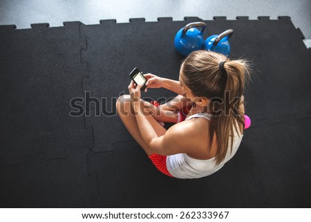 Young woman with smartphone at the gym,workout break  - stock photo