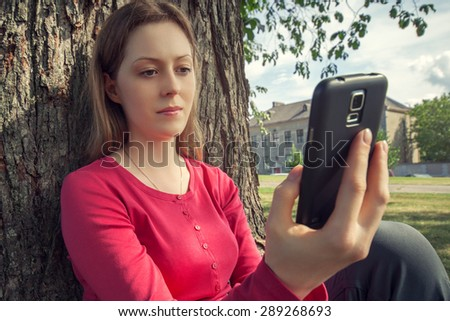 Young woman with smartphone in park sitting at big tree. - stock photo