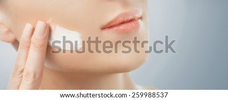 Young woman with smooth skin applying cream. Beauty and skincare concept - stock photo
