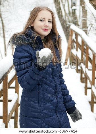 young woman with snowball in blue coat outdoors in snow garden - stock photo