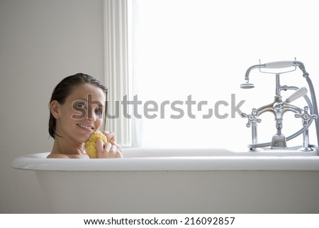 Young woman with sponge in bath, smiling, portrait - stock photo