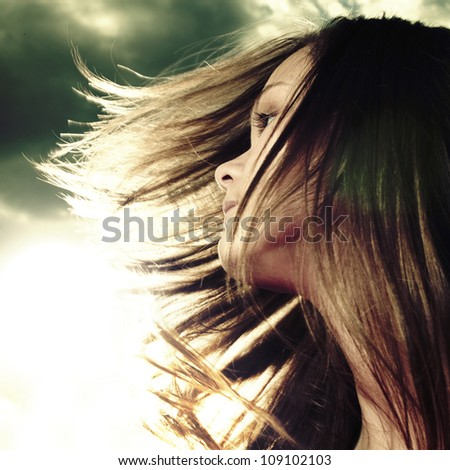 Young woman with stormy clouds background - stock photo