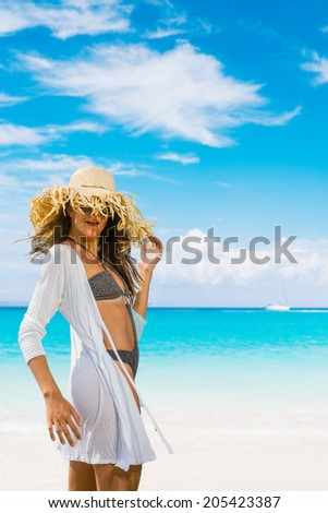 Young woman with straw hat  at the beach in the summertime - stock photo